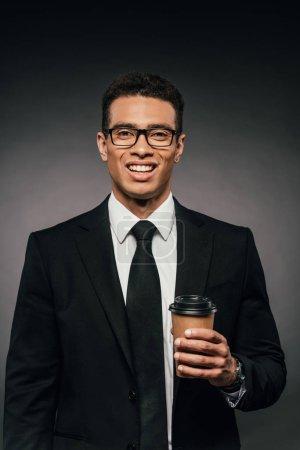 Foto de Guapo hombre de negocios afroamericano sonriente en vasos y traje sosteniendo café para ir en el fondo oscuro - Imagen libre de derechos