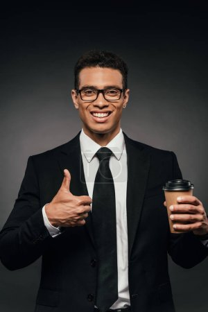 handsome smiling african american businessman in glasses and suit holding coffee to go and showing thumb up on dark background
