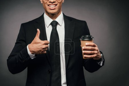 Photo for Cropped view of smiling african american businessman in suit holding coffee to go and showing thumb up on dark background - Royalty Free Image