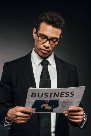 Photo for Handsome african american businessman in glasses and suit reading business newspaper on dark background - Royalty Free Image