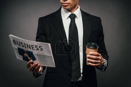 Photo for Partial view of handsome african american businessman in suit reading business newspaper and holding coffee to go on dark background - Royalty Free Image
