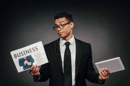 Foto de Confundido hombre de negocios afroamericano en gafas y traje sosteniendo periódico de negocios y tableta digital en fondo oscuro - Imagen libre de derechos