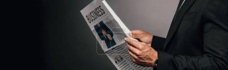 Photo pour Vue recadrée de l'homme d'affaires américain africain lisant le journal d'affaires sur le fond foncé, projectile panoramique - image libre de droit