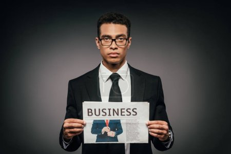Foto de Guapo hombre de negocios afroamericano en gafas y traje sosteniendo periódico de negocios en fondo oscuro - Imagen libre de derechos