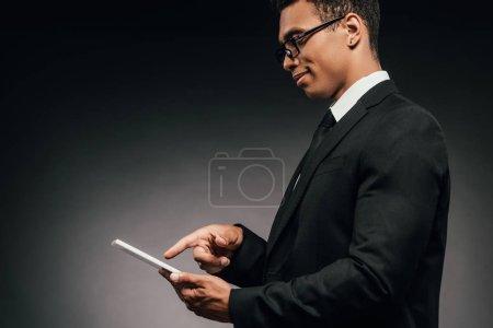Photo pour Vue de côté de sourire l'homme d'affaires américain africain utilisant la tablette numérique sur le fond foncé - image libre de droit