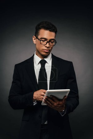 Photo for African american businessman in glasses using digital tablet on dark background - Royalty Free Image