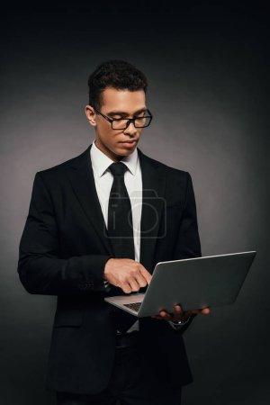 Photo pour Homme d'affaires américain africain utilisant l'ordinateur portatif sur le fond foncé - image libre de droit