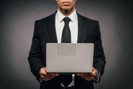 Photo pour Vue partielle de l'homme d'affaires américain africain retenant l'ordinateur portatif sur le fond foncé - image libre de droit