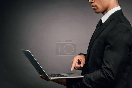 Photo pour Vue partielle de l'homme d'affaires américain africain utilisant l'ordinateur portatif sur le fond foncé - image libre de droit