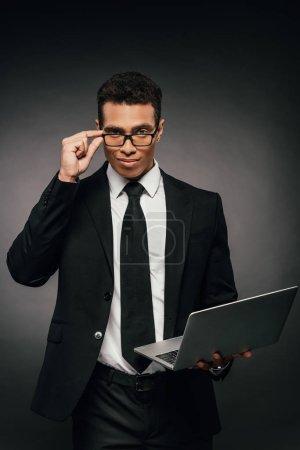 Photo pour Beau homme d'affaires américain africain dans des glaces et l'ordinateur portatif de fixation de costume sur le fond foncé - image libre de droit