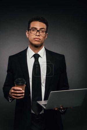Photo pour Homme d'affaires américain africain retenant l'ordinateur portatif et la tasse de papier sur le fond foncé - image libre de droit