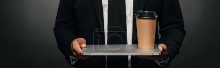 Photo for Cropped view of african american businessman holding laptop and paper cup on dark background, panoramic shot - Royalty Free Image