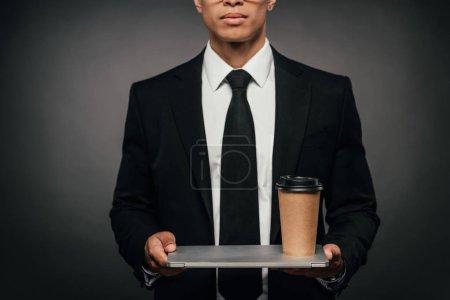 Photo pour Vue recadrée de l'homme d'affaires américain africain retenant l'ordinateur portatif et la tasse de papier sur le fond foncé - image libre de droit