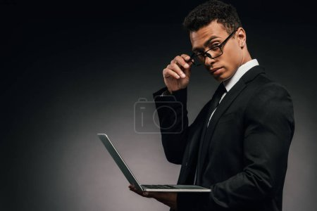 Photo for African american businessman holding laptop and looking at camera on dark background - Royalty Free Image