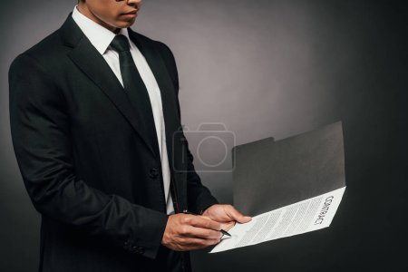 Photo for Cropped view of african american businessman signing contract on dark background - Royalty Free Image