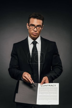 Photo for African american businessman showing contract on dark background - Royalty Free Image