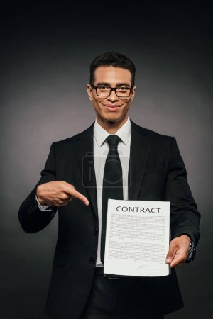 Photo for Smiling african american businessman pointing with finger at contract on dark background - Royalty Free Image