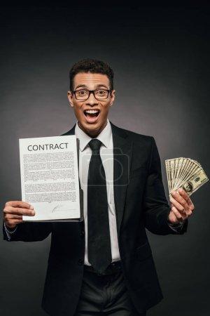 Photo pour Heureux homme d'affaires afro-américain montrant contrat et tenant de l'argent sur fond sombre - image libre de droit