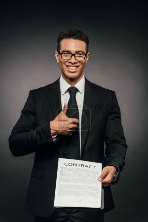 Photo for Happy african american businessman showing contract and thumb up on dark background - Royalty Free Image