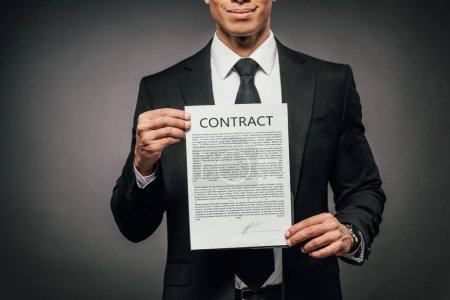 Photo for Partial view of cheerful african american businessman showing contract on dark background - Royalty Free Image