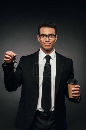 Photo pour Homme d'affaires américain africain heureux retenant des clefs de voiture et du café pour aller sur le fond foncé - image libre de droit