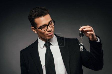 Photo pour Homme d'affaires afro-américain regardant les clés de voiture sur fond sombre - image libre de droit