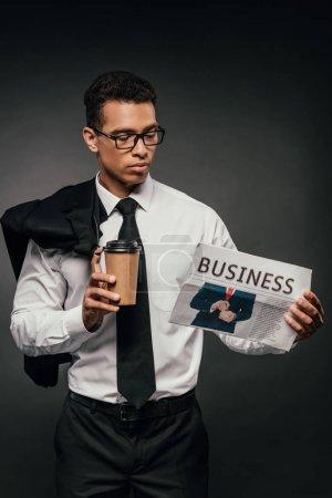 Photo pour Homme d'affaires afro-américain tenant blazer, tasse en papier et journal d'affaires sur fond sombre - image libre de droit