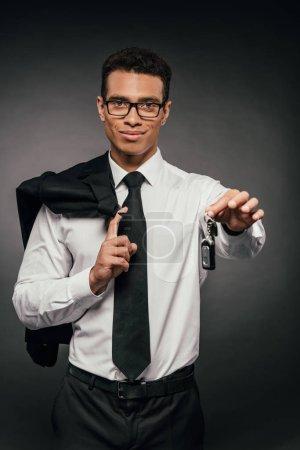 Photo pour Homme d'affaires américain africain de sourire retenant le blazer et les clefs de voiture sur le fond foncé - image libre de droit