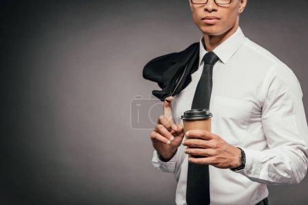 Foto de Vista recortada del empresario afroamericano sosteniendo blazer y café para ir en el fondo oscuro - Imagen libre de derechos
