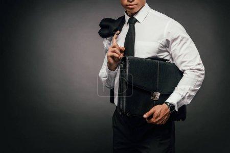 Photo pour Vue recadrée de l'homme d'affaires afro-américain tenant blazer et mallette en cuir sur fond sombre - image libre de droit