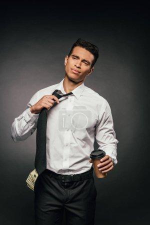 Photo pour Homme d'affaires américain africain avec l'argent comptant dans le café de fixation de poche pour aller et délier la cravate sur le fond foncé - image libre de droit