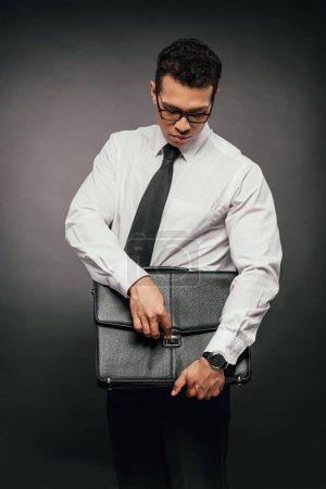 Photo pour Homme d'affaires afro-américain fermeture valise en cuir sur fond sombre - image libre de droit