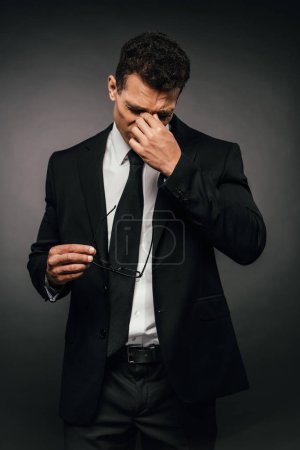 Photo for Tired african american businessman in suit rubbing his eyes on dark background - Royalty Free Image