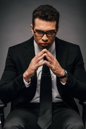 Foto de Tenso hombre de negocios afroamericano en traje y gafas sobre fondo oscuro - Imagen libre de derechos
