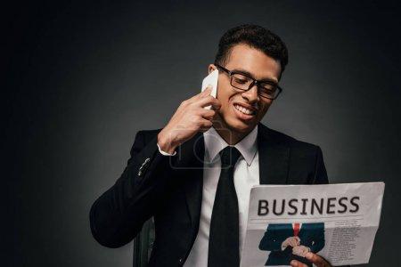 Foto de Hombre de negocios afroamericano feliz en traje hablando en el teléfono inteligente mientras lee el periódico de negocios en el fondo oscuro - Imagen libre de derechos
