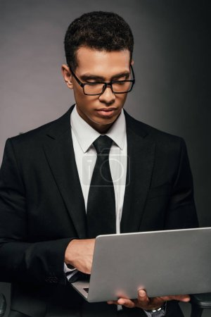 Photo for Successful african american businessman using laptop on dark background - Royalty Free Image