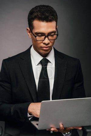 Photo pour Homme d'affaires afro-américain réussi en utilisant un ordinateur portable sur fond sombre - image libre de droit