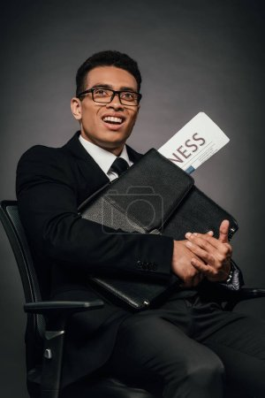 Photo for Successful african american businessman holding briefcase and business newspaper on dark background - Royalty Free Image