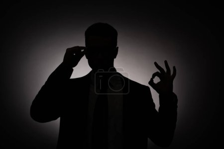Photo for Black silhouette of businessman showing ok sign with back light - Royalty Free Image