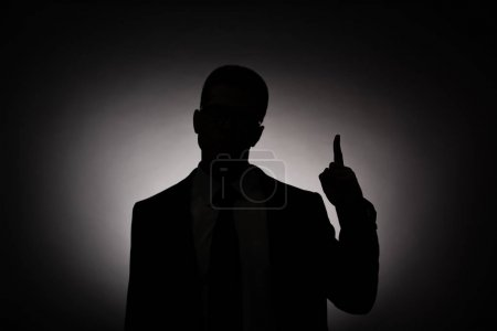 Photo for Black silhouette of businessman showing idea sign with back light - Royalty Free Image