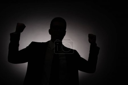 Photo for Black silhouette of businessman showing yes gesture with back light - Royalty Free Image