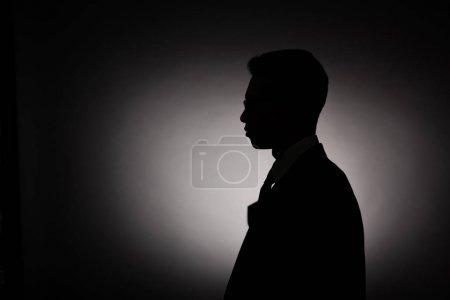 Photo pour Vue latérale de la silhouette noire de l'homme d'affaires avec la lumière arrière - image libre de droit