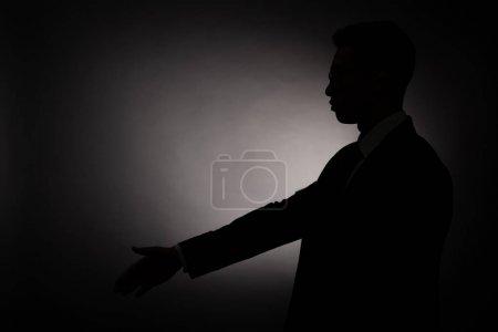 Foto de Vista lateral de la silueta negra del hombre de negocios haciendo gesto de saludo con luz trasera - Imagen libre de derechos