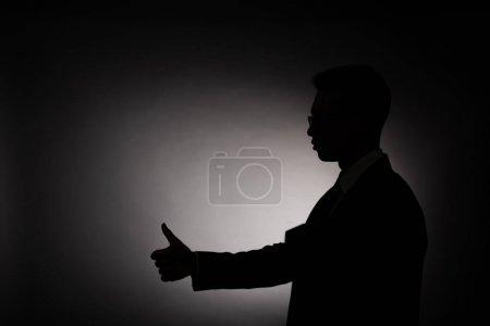 Photo pour Vue de côté de la silhouette noire de l'homme d'affaires affichant le pouce vers le haut avec la lumière arrière - image libre de droit
