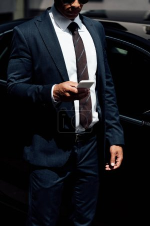 Photo for Cropped view of african american businessman in suit using smartphone at sunny day - Royalty Free Image