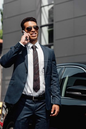 Photo for African american businessman in suit and sunglasses talking on smartphone at sunny day near car - Royalty Free Image