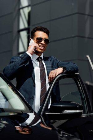 Photo pour Homme d'affaires américain africain dans le procès et les lunettes de soleil parlant sur le smartphone près de la voiture au jour ensoleillé - image libre de droit
