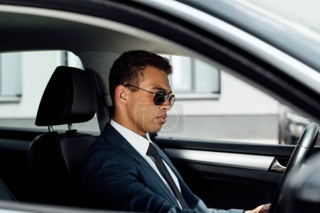 Photo for African american businessman in suit and sunglasses driving car at sunny day - Royalty Free Image