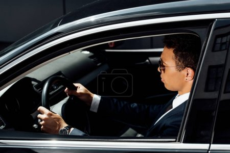 Photo for Side view of african american businessman in suit and sunglasses driving car at sunny day - Royalty Free Image