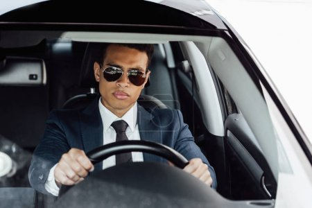 Photo for African american businessman in suit and sunglasses driving car - Royalty Free Image